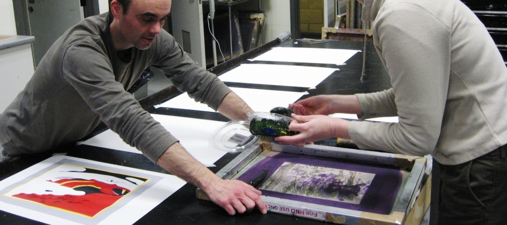 Image of Ian McDonald hand printing his screenprints